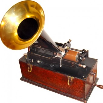 Edison cylinder phonograph, Suitcase Model. Appears to be a wooden box with a size crank handle, over which is positioned a wax cylinder connected to a brass microphone that flares like a tumphet or funnel.
